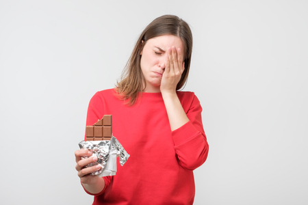 Sad young woman tired of diet restrictions holding sweet chocolate isolated on gray wall background. Nutrition concept. Feelings of guilt
