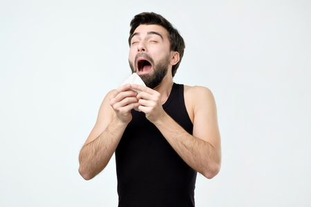 Hispanic young man with black beard being ill sneezing. Standard-Bild