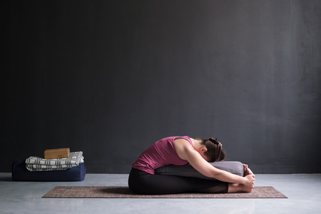 woman practicing yoga, doing Seated forward bend pose, using bolster. Stockfoto