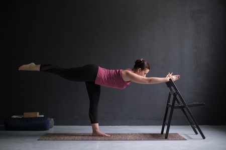 Woman show warrior asana using chair in studio background