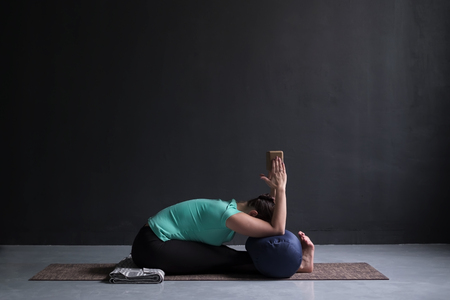 woman practicing yoga, Seated forward bend pose, using block and bolster