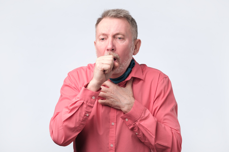 European gentleman in red shirt coughing because of pulmonary diseas