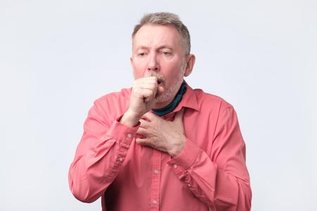 Gentleman européen en chemise rouge toussant à cause de maladies pulmonaires