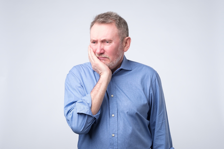 Senior man in blue shirt suffering tooth pain