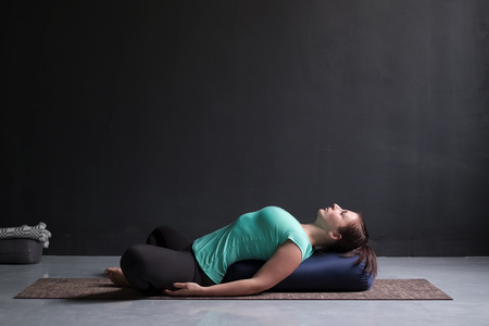 Woman practicing yoga concept, lying in Reclined Butterfly exercise