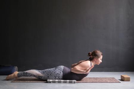 Sporty woman practicing yoga, doing Salabhasana pose variation