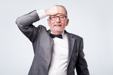 Senior man in formal suit with bow tie surprised with hand on head for mistake