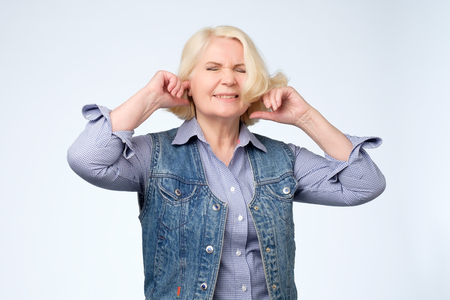 unhappy stressed out senior female making wry face, plugging ears with fingers