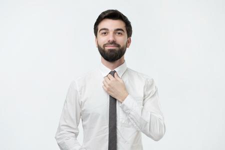 Man in shirt dressing up and adjusting tie on neck Banco de Imagens