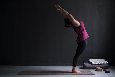 European woman on a yoga mat doing the upward salute pose.