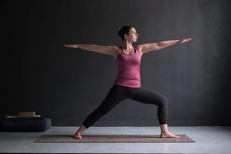 Woman practicing yoga, standing in Warrior Two exercise, Virabhadrasana II pose