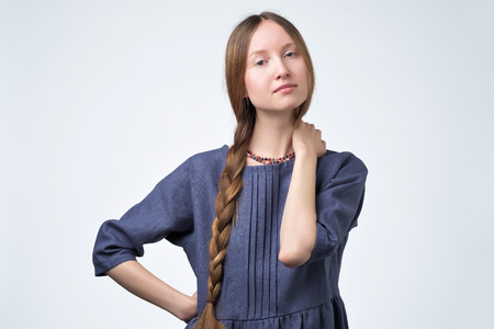 Headshot of attractive russian female in blue dress with braid hair, smiling with confident and friendly expression