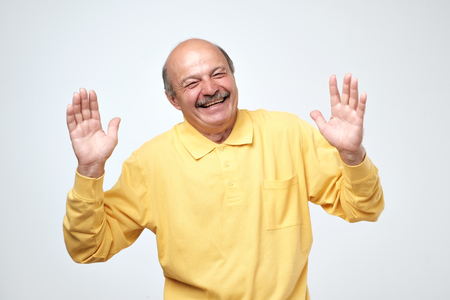Portrait of senior happy man with hands lifted upwards. Positive facial human emotion