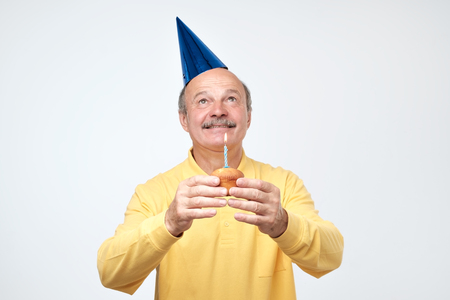 Birthday mature man with party hat is happy on his party isolated on white background. Positive facial emotion