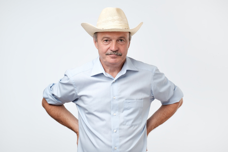 mature man wearing cowboy in studio. He is looking at camera with confidence. Texas citizen concept.