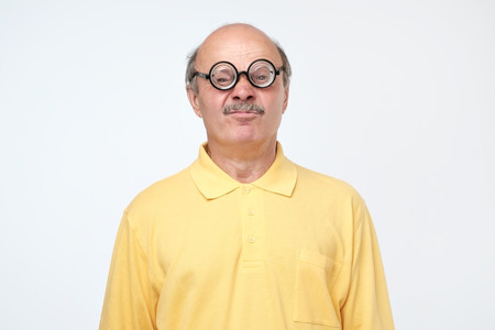 Funny senior hispanic man looking at camera wearing funny glasses. Negative facial emotion