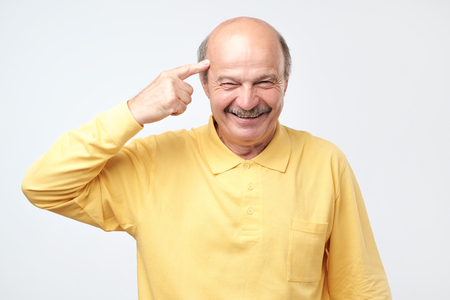 Handsome middle age hoary senior man smiling pointing to head with one finger, great idea or thought, good memory