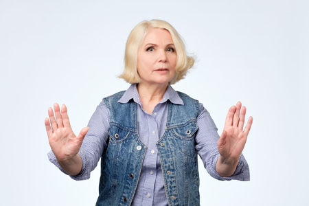 Serious senior european woman standing with outstretched hand showing stop gesture isolated over white background
