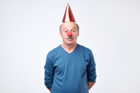 Confused man on clown hat looks with hesitant expression, isolated over white background