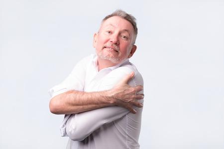 Smiling senior man holding hugging himself isolated on grey wall background.