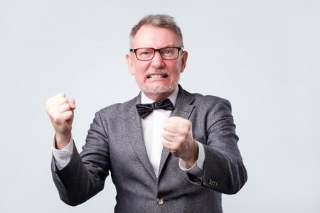 Handsome elegant senior man angry and mad raising fist up Stock Photo