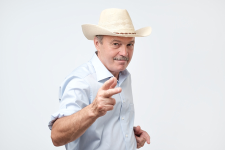 mature man wearing cowboy in studio. He is looking at camera with confidence and pointing at you. Texas citizen concept.