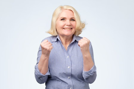 Cheerful granny with toothy smile raised hands and showing successful sign celebrate goal isolated on white background