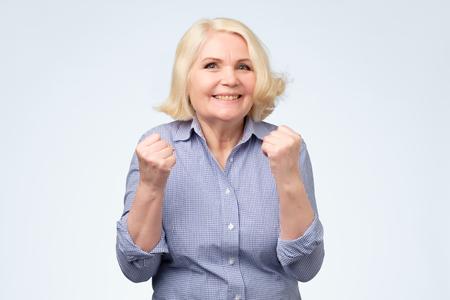 Fröhliche Oma mit zahnigem Lächeln hob die Hände und zeigte erfolgreiches Zeichen, um das Ziel isoliert auf weißem Hintergrund zu feiern Standard-Bild
