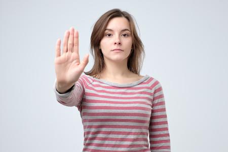 Jeune femme caucasienne sérieuse montrant le geste d'arrêt avec sa main. Prise de vue en studio