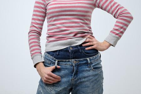 Frau, die zwei Jeanshosen trägt. Seltsame und seltsame moderne Mode. Kein Gesicht. Sie ist sehr schlampig Standard-Bild