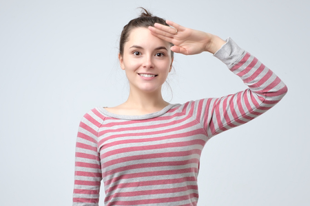 Young european woman saluting showing her patriotism. Ready to protect her country. Archivio Fotografico