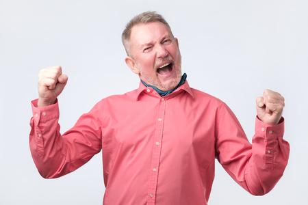 Homme senior excité en chemise rouge très heureux de gagner, gesticulant avec les poings. Émotion faciale positive
