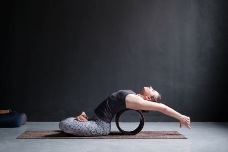 Sporty fit woman practices yoga asana Matsyasana, fish pose variation with wheel in studio