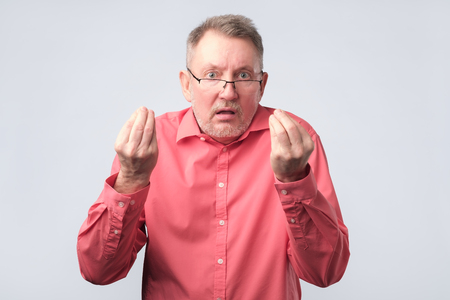 Senior man looking angry showing italian gesture. He is annoyed, talking to his family
