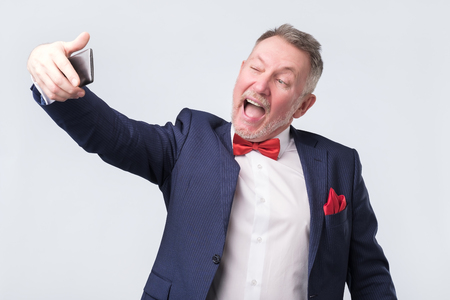 Senior man dressed in blue suit and red bow tie making a selfie by phone. Studio shoot. Stockfoto