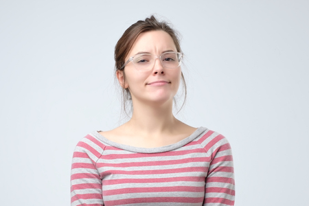 Skeptical woman in glasses is not sure and does not believe you. Confused and upset facial emotion.