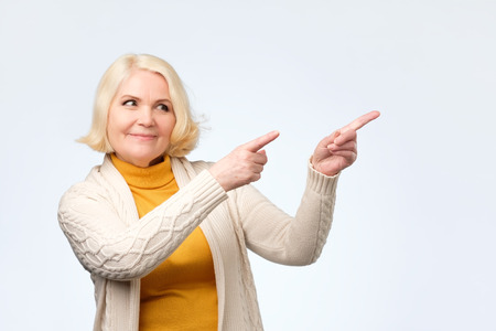 Happy blonde senior woman smiling pointing fingers away, showing something interesting and exciting on studio wall