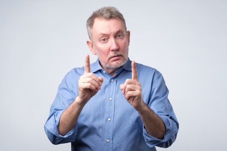 Experienced senior man in blue shirt showing index fingers up, giving advice or recommendation. Warning sign at studio shoot