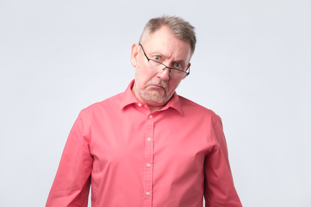 Elderly man in red shirt and glasses upset and distressed by the size of his pension. Negative facial emotion.