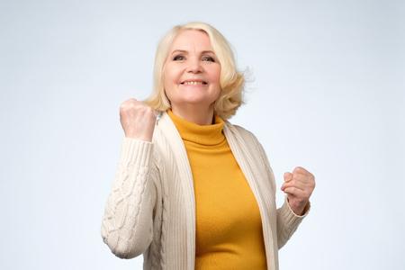 Glücklicher älterer Frauensieger, der ihre Fäuste ballt. Feiern, Ziele erreichen und Träume wahr werden lassen Konzept