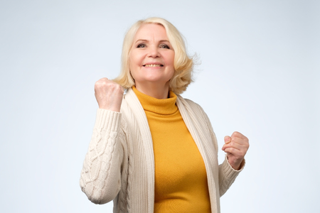 Happy senior woman winner clenching her fists. Celebrating, achieving goals and making her dreams come true concept