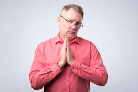S'il vous plaît aidez-moi concept. Un homme âgé en chemise rouge a besoin d'aide. Prise de vue en studio