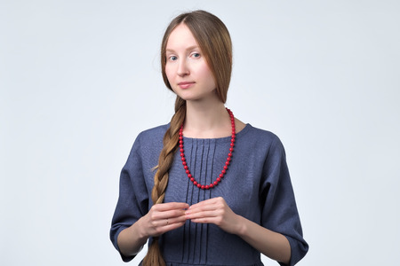 Lack of confidence. Shy young woman in blue dress with red beads feels awkward. Human emotion body language