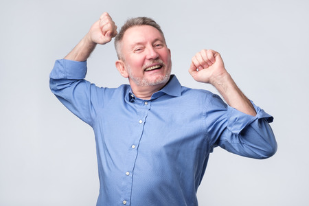 Yeah, good work man. Happy cheerful senior strong man, raising clenched fists in hooray gesture, triumphing from successful deal or great news