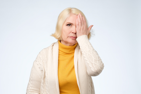 Senior woman covering one eye with her hand as she stares at the camera with a serious expression. Control of eyesight at old age.