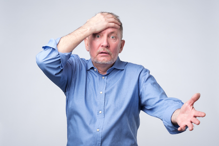 Senior caucasian man surprised with hand on head. He is upset for mistake, remember error. Bad memory concept. Studio shoot