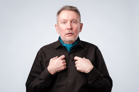 Mature man pointing to himself with question if he did something wrong. Stock fotó