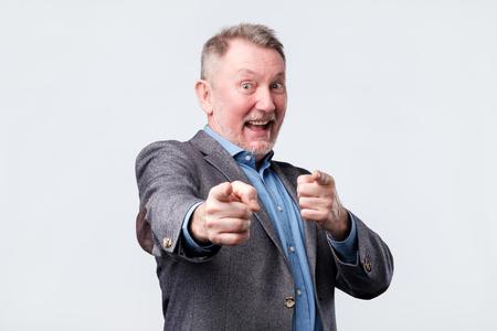Hey you concept. Happy senior man pointing at you. Фото со стока