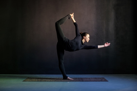 Woman practicing yoga, stretching in Natarajasana exercise