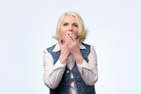 Middle age pretty blonde european woman over isolated background shocked covering mouth with hands. Secret concept. Studio shot